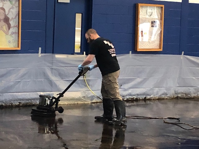 man using machine to refinish floor